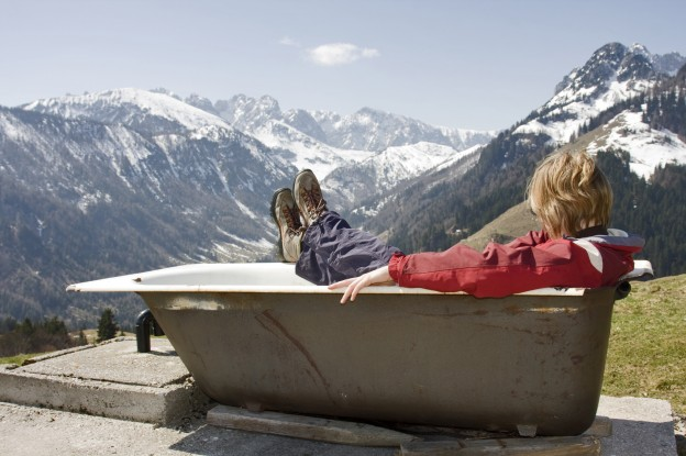 frau in badewanne schaut zu den alpen