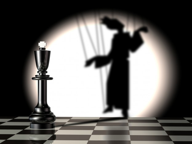Black chess king with puppet's shadow